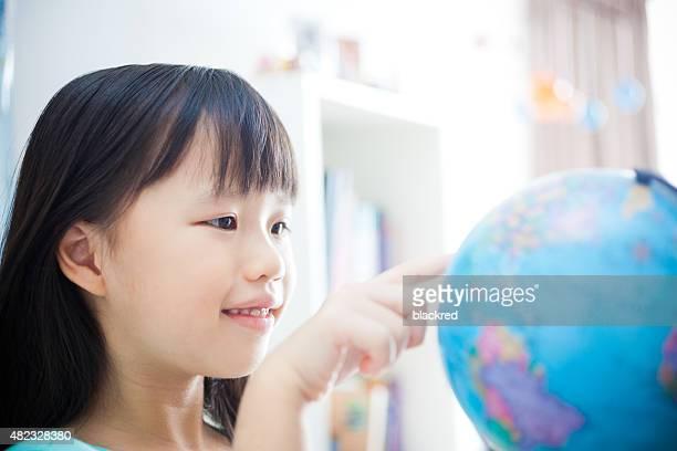 Kleines Mädchen lernen und zeigt auf eine Welt
