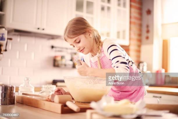 Little girl learning how to make proper dough. Krakow, Poland