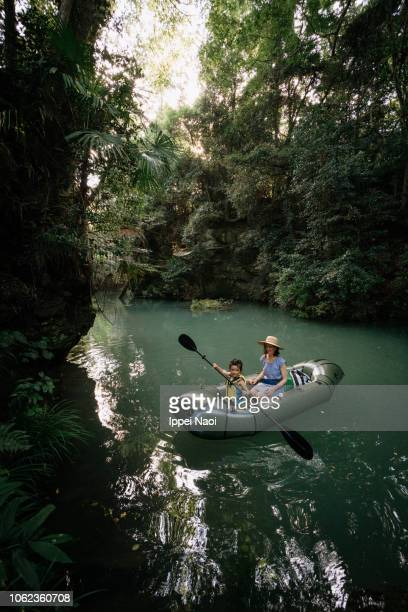 Little girl learning how to paddle kayak on river in forest, Japan
