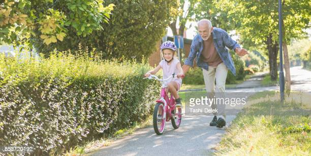 little girl learning ride a bike with grandfather - grandfather stock pictures, royalty-free photos & images