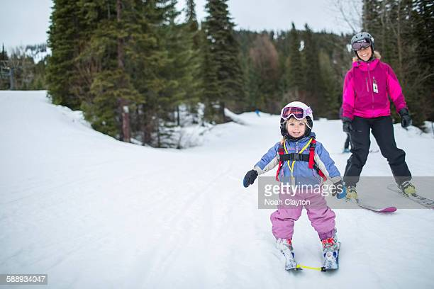 Little girl (2-3) learning skiing with mother