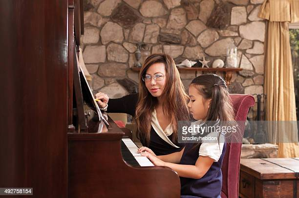 小さな女の子は彼女の学習ピアノの先生