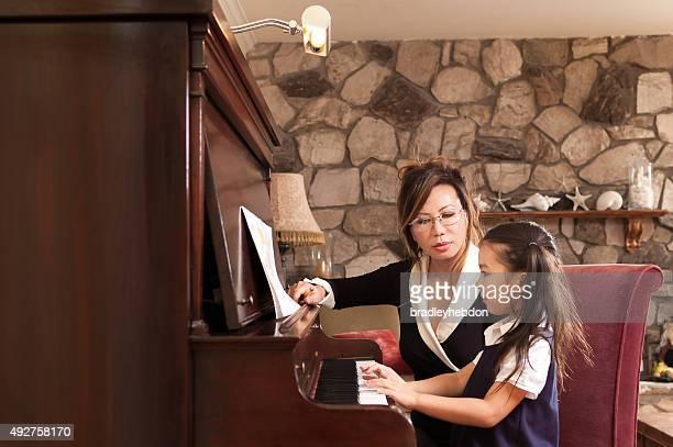 Petite fille d'apprentissage avec son professeur de piano