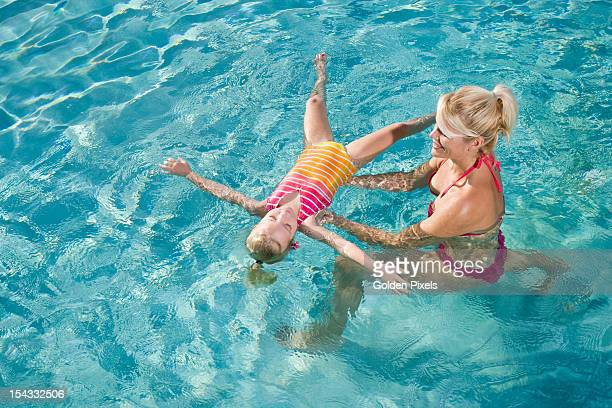 Little girl learning to float in swimming pool