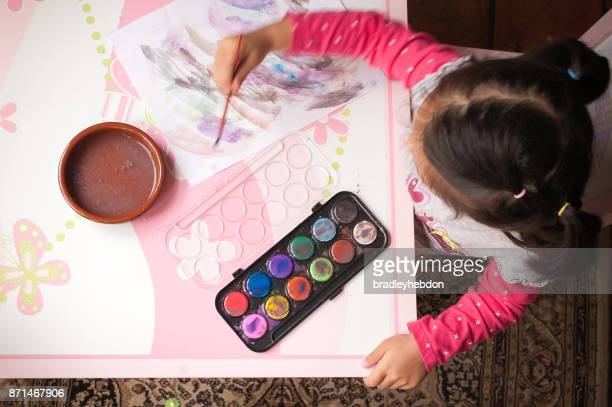 Little girl learning to paint with watercolors