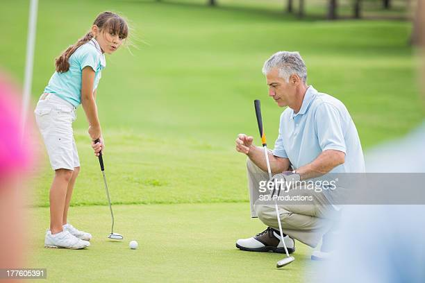 Little girl learning to putt during golf lesson with pro