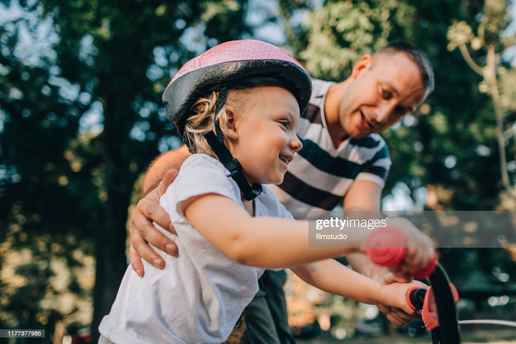 Little Girl Learning To Ride Bicycle With Her Dad : Stock Photo