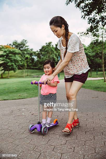 little girl learning to ride push scooter with mom - girls with short skirts - fotografias e filmes do acervo