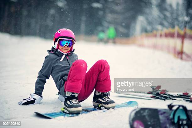 Little girl learning to snowboard