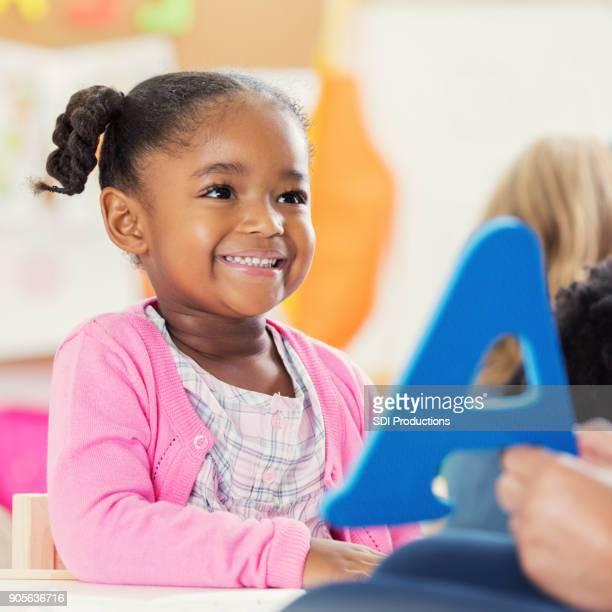 女の子が幼稚園の中にアルファベットを学習します。 - 綴り ストックフォトと画像