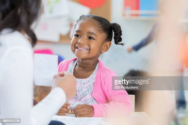 Little girl learns with flash cards at preschool