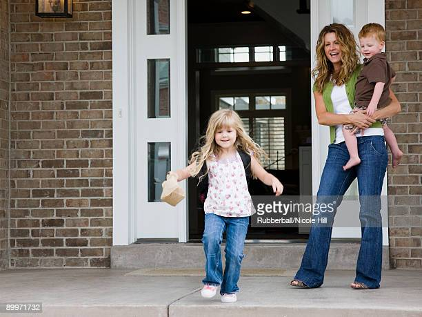 little girl leaving for school as mother watches
