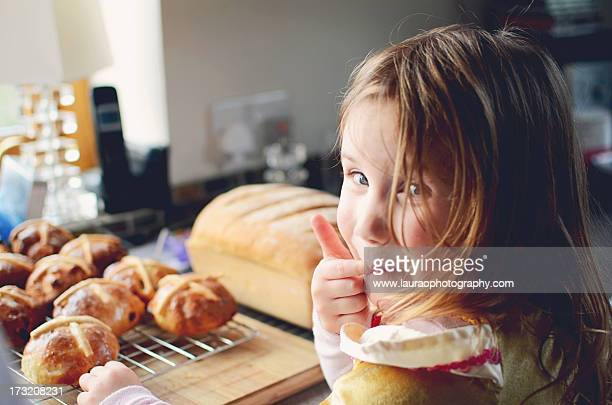 little girl licking fingers at easter - hot cross bun stock pictures, royalty-free photos & images