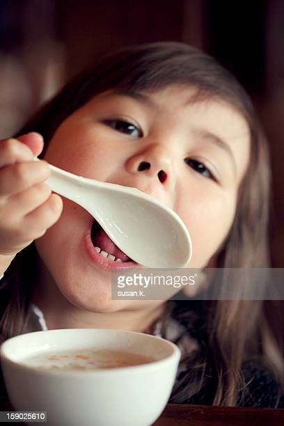 Little girl licking her spoon at breakfast.