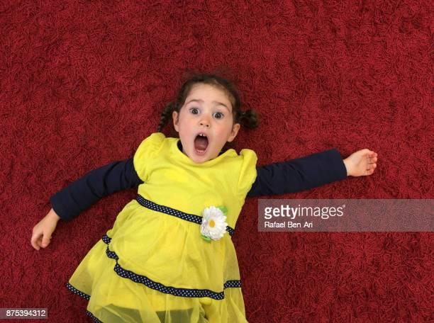 Little girl lies on a red carpet