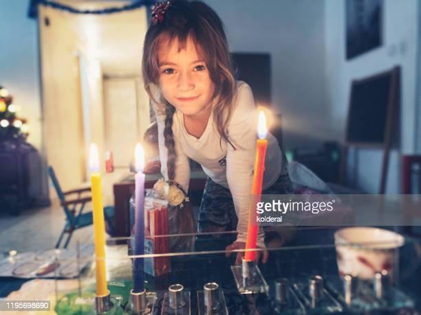 little girl lighting menorah at home - menorah stock pictures, royalty-free photos & images