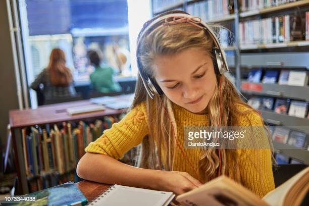 little girl listening to music and studying - poetry literature stock pictures, royalty-free photos & images