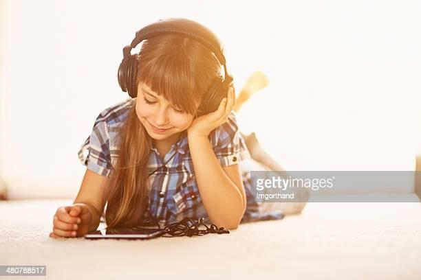 Niña escuchando la música en los comprimidos