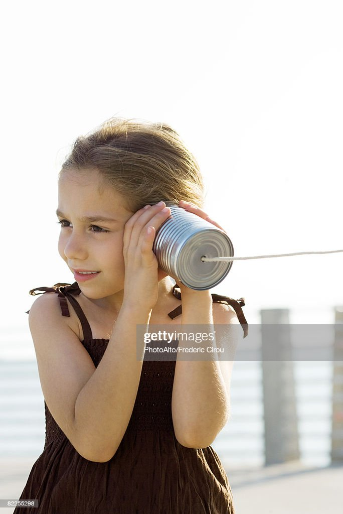 Little girl listening to tin can phone : Stock Photo