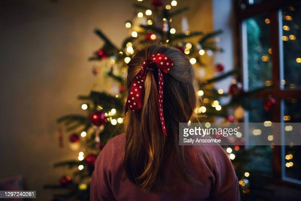 little girl looking at a christmas tree - tree stock pictures, royalty-free photos & images