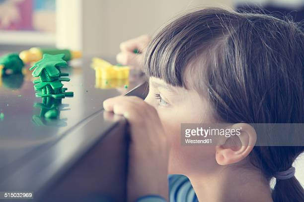 Little girl looking at figure of green modeling clay