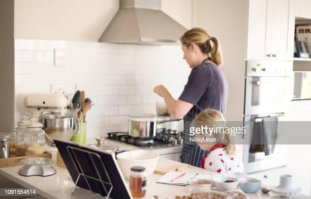 kleines mädchen ihrer mutter kochen zu betrachten. - hausfrau stock-fotos und bilder