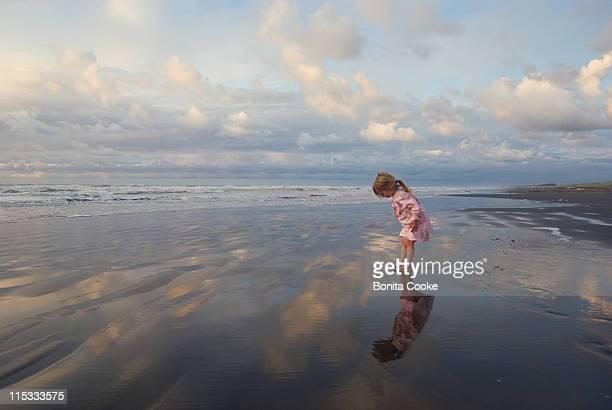 little girl looking at her reflection at beach - só uma menina - fotografias e filmes do acervo