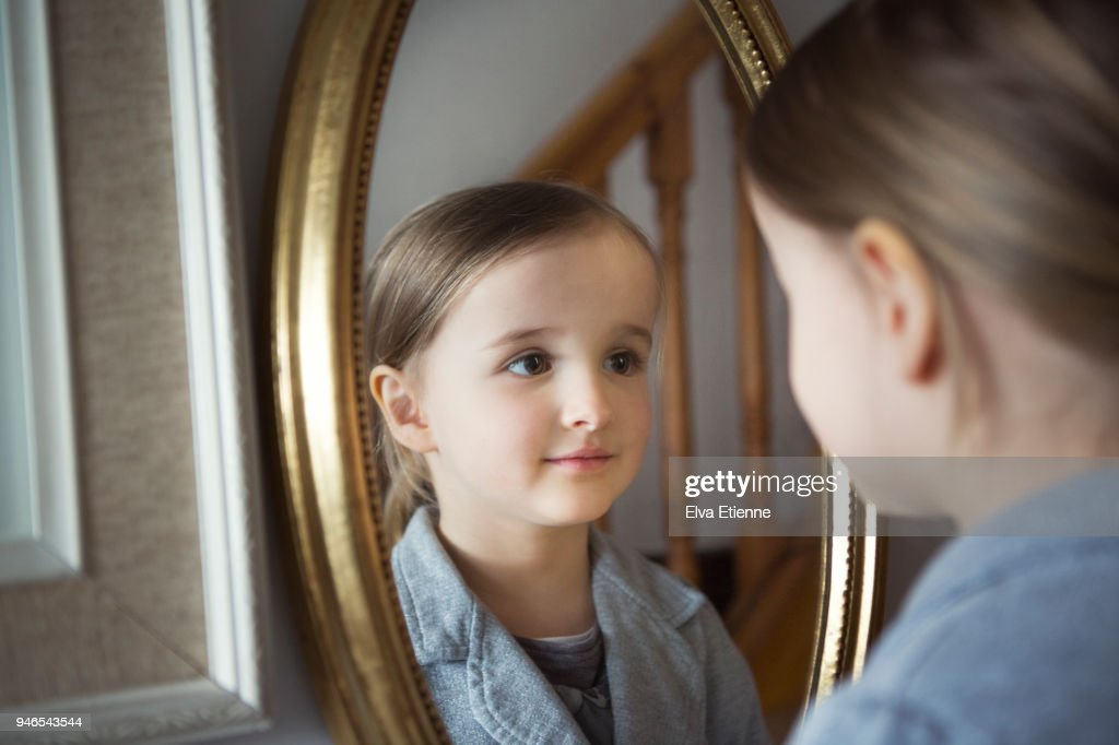 Little girl looking at her reflection in an oval shaped framed mirror : Stock Photo