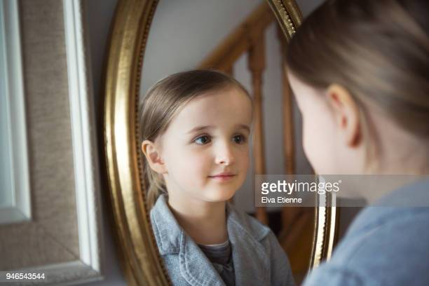 little girl looking at her reflection in an oval shaped framed mirror - girl in mirror stock-fotos und bilder