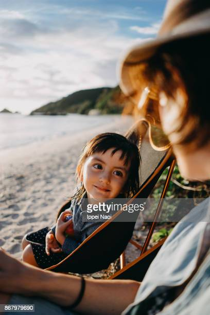 Little girl looking at mother admiringly at beach