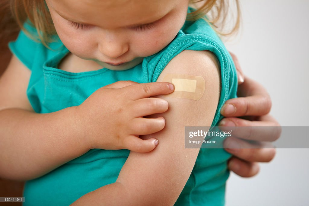 Little girl looking at plaster where she has had an injection : Stock Photo
