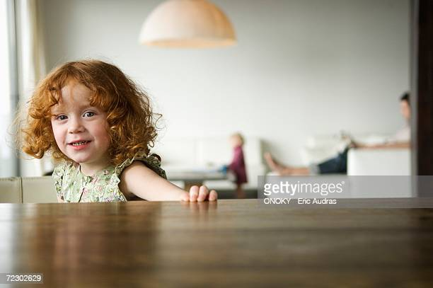 Little girl looking at the camera, coffee table in the foreground