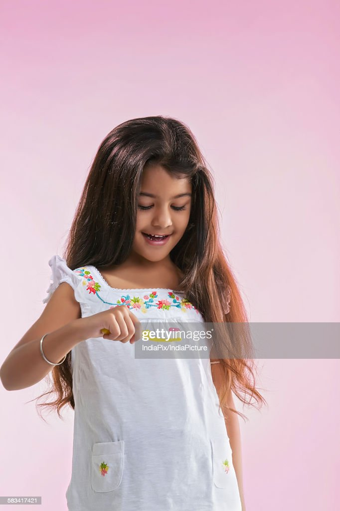 Little girl looking at toothbrush with toothpaste : Stock Photo