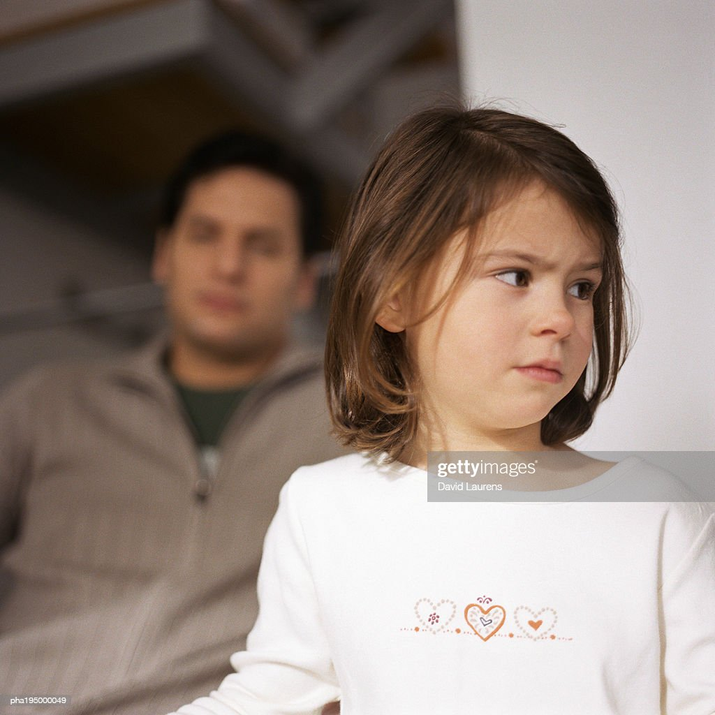 Little girl looking away, head and shoulders, close-up,  man in background, blurred. : Stockfoto