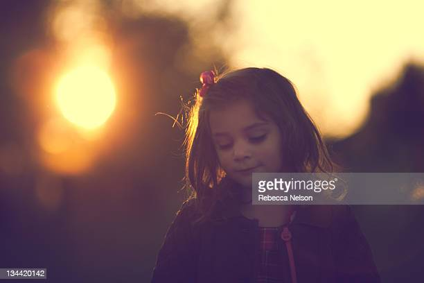 little girl looking downward at sunset - rebecca nelson stock pictures, royalty-free photos & images