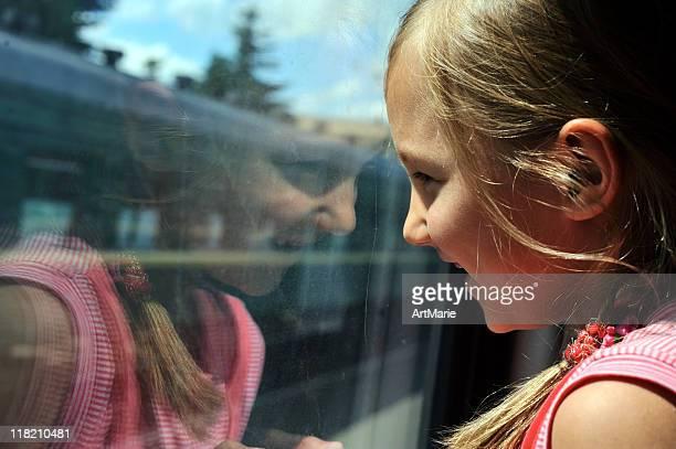 Petite fille à la recherche dans la fenêtre