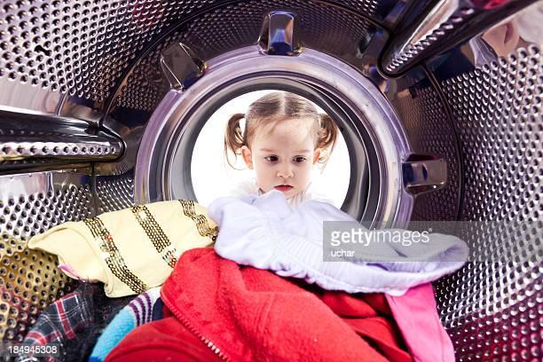 Niña mirando en la máquina de lavado