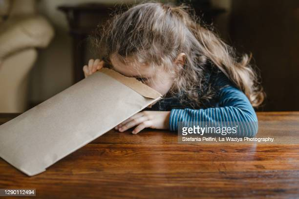 little girl looking into a cardboard package - receiving stock pictures, royalty-free photos & images