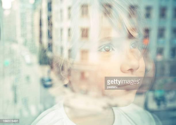 Kleines Mädchen schaut aus dem Fenster auf die Straße.