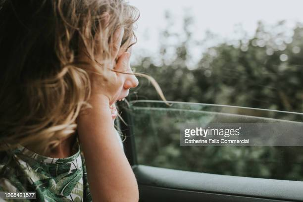 little girl looking out of a car window and pushes her hair out of her face as the wind blows through her hair - car stock pictures, royalty-free photos & images