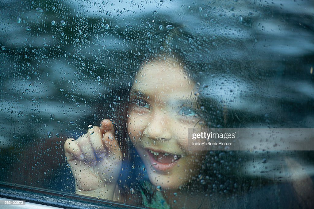 Little girl looking out of car window : Stock Photo