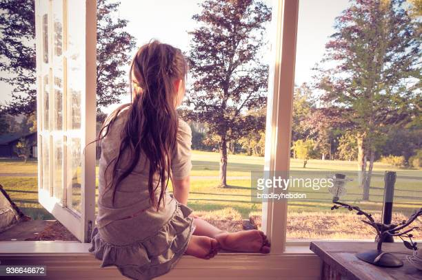 Little girl looking out of her bedroom window alone