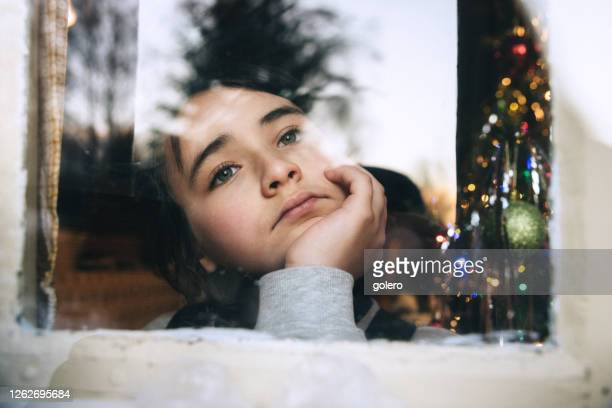 little girl looking out of the window waiting for santa claus to come - desiderio foto e immagini stock