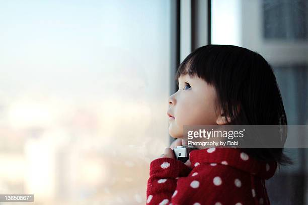 little girl looking out of window - curiosity stock pictures, royalty-free photos & images