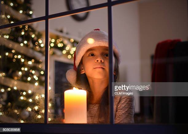 little girl looking out the window on christmas - bougie espoir photos et images de collection
