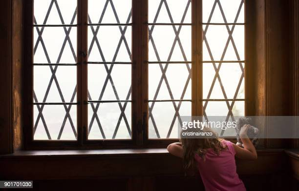 little girl looking out the window - harassment stock pictures, royalty-free photos & images