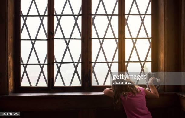 little girl looking out the window - adopción fotografías e imágenes de stock