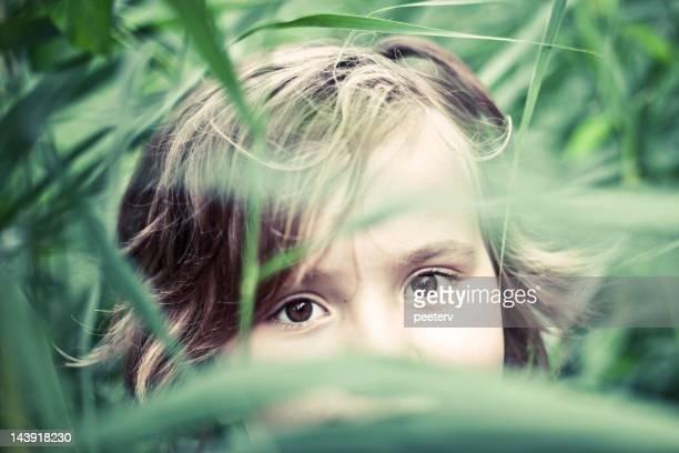 Kleines Mädchen Blick durch thatch verlässt.