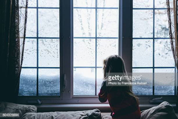 Little girl looking out window at snow
