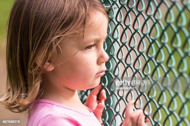 little girl looking through a fence - orphan stock pictures, royalty-free photos & images